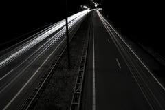 Headlight streaks on dark road Stock Photography