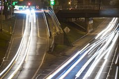 Headlight trails on a freeway. Long exposure of a motorway traffic at night - light trails painted in the shot Stock Photos