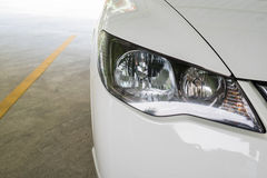 Headlight of a white modern car at parking lot Royalty Free Stock Photo