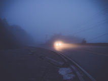 Headlights of car driving in fog Stock Photo