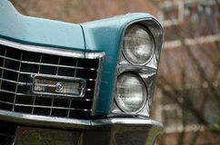 Headlights and radiator of a classic American car under rain on Royalty Free Stock Image