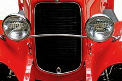 Headlights of red vintage car. Front view and headlights of a shiny red hot rod or classic vehicle Stock Image
