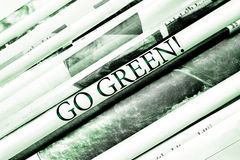 "Headline ""Go green!"" over folded newspapers stock image"