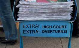 Headline high court overturns. Newspaper stack - take one of these newspaper in the subway entrance Stock Images