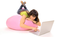 Headlong with laptop. Girl lying headlong with laptop on pink sack Stock Images