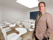 Headmaster. Serious looking man on a classroom Royalty Free Stock Image