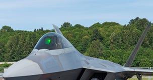 Headon del rapace F22 con il primo piano della cabina di pilotaggio che sta nel fondo verde fertile fotografie stock libere da diritti