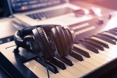 Headphone on home Music studio keyboard. Black headphone on home Music studio keyboard stock image