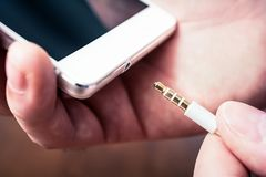 Headphone Jack Of som en vit Smartphone får pluggad in en vit hörlurar med mikrofonkabel arkivbild