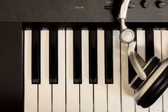 Headphone on key piano background. Royalty Free Stock Images
