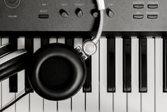 Headphone on key piano background. The headphone on key piano background Royalty Free Stock Photography