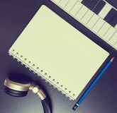 Headphone Keyboard and for blank book for music writing. Song writing equipment in vintage tone. Headphone Keyboard and note book for music writing. Song Royalty Free Stock Photo
