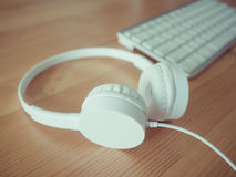 Headphone and keyboard. White headphone and keyboard on wooden desk Stock Image