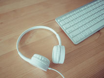 Headphone and keyboard. White headphone and keyboard on wooden desk Stock Photography