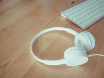 Headphone and keyboard. White headphone and keyboard on wooden desk Stock Images