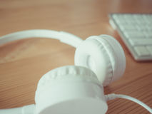 Headphone and keyboard. White headphone and keyboard on wooden desk Royalty Free Stock Photo