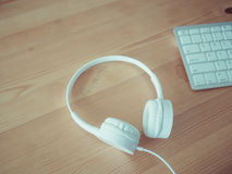 Headphone and keyboard. White headphone and keyboard on wooden desk Royalty Free Stock Photography