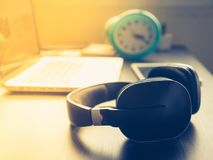 Headphone with Laptop on office desk and sunshine in afternoon stock image