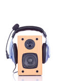 Headphone on loudspreaker. Headphone with microphone on loudspeaker box - isolated on white Royalty Free Stock Photos