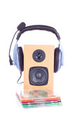 Headphone on loudspreaker. Headphone with microphone on loudspeaker box and a group of disks Stock Image