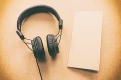 Headphone med brunt och vitbokanmärkning på det wood skrivbordet i musikstudio Royaltyfri Bild