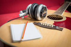 Headphone and Notebook and pencil on guitar Royalty Free Stock Images