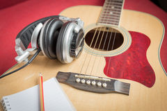 Headphone and Notebook and pencil on guitar Stock Photo
