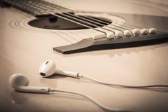 Headphone på gitarrbakgrund Royaltyfria Bilder