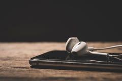 Headphone and phone media portable on dark tone. Stock Photography