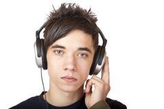 headphone som allvarligt ser den male tonåringen Royaltyfria Bilder