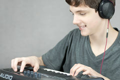 Headphone Wearing Teen Adjusts Keyboard Stock Images