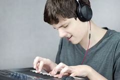 Headphone Wearing Teen Plays Keyboard Royalty Free Stock Photo