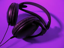 Headphones. A pair of black headphones on a bright purple background stock photos