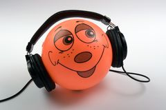 Headphones. On ball with face on it Stock Photography