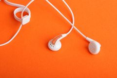 Headphones. White headphones liners on an orange background Royalty Free Stock Photography