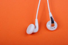 Headphones. White headphones liners on an orange background Royalty Free Stock Photos