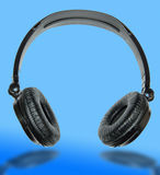Headphones. Of black color on a dark blue background with reflection Stock Photos