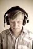Headphones. Senior male listening to music through headphones royalty free stock photo