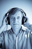 Headphones. Senior male listening to music through headphones royalty free stock image