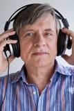 Headphones. Senior male listening to music through headphones royalty free stock photos