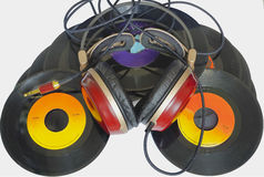 Headphones arranged over some old 45 rpm vinyl. Headphones arranged over some old 45 rpm records Royalty Free Stock Photos