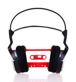 Headphones on a audio cassette. Headphones with audio cassette isolated on white background Stock Image