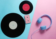 Headphones, audio cassette, lp records. On pink blue background. Retro culture. Creative Flat lay. Top view stock photography