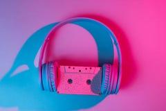 Headphones with audio cassette. 80s. Retro wave, pink blue neon light, ultraviolet. Top view, minimalism stock photo