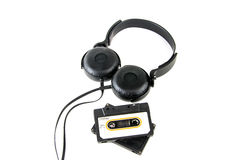 Headphones with audio cassette on white Royalty Free Stock Photos