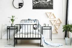 Teenager`s bedroom with triangles. Headphones on bed with bright bedding between nightstands with clock and plant in teenager`s bedroom with triangles on the Royalty Free Stock Photography