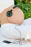 Headphones on belly Royalty Free Stock Photo