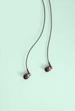 Headphones. Black In-Ear Headphones on Colored Background Stock Photo