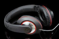 Headphones. Black headphones for listening to music lying on a shiny surface Royalty Free Stock Photo