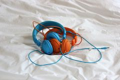 Headphones. Blue pair and orange pair of headphones stock photo